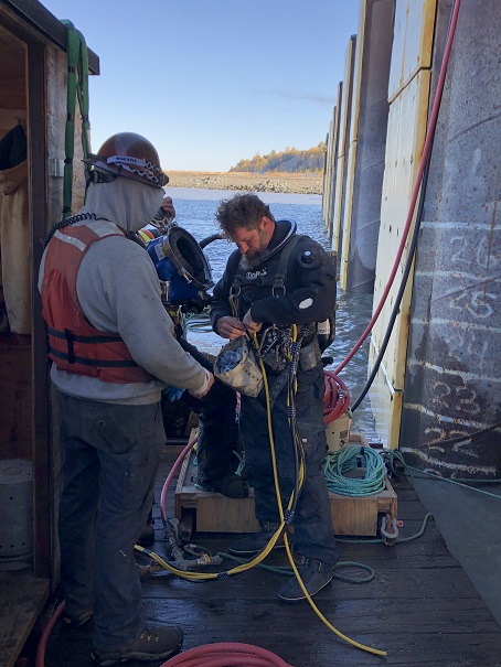 diver suits up to install pile jackets